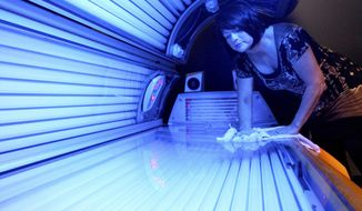 FILE - In this April 2, 2014 file photo, Teresa Lynch, owner of Dynamic Tanning in DeKalb, Ill., wipes down a tanning bed. Tanning beds and sun lamps will carry new warnings that they should not be used by anyone under age 18, under a government action Thursday, May 29, 2014, aimed at reducing rising rates of skin cancer linked to the radiation-emitting devices. (AP Photo/Daily Chronicle, Monica Maschak, File)  MANDATORY CREDIT