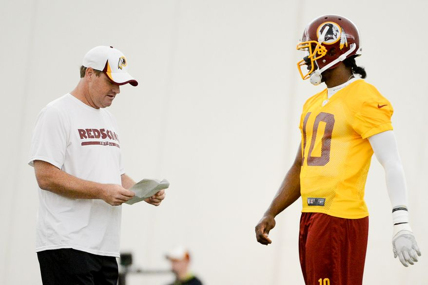 Washington Redskins quarterback Robert Griffin III (10), right, talks with Washington Redskins head coach Jay Gruden, left, as the Washington Redskins hold their Organized Team Activities, Ashburn, Va., Thursday, May 29, 2014. (Andrew Harnik/The Washington Times)