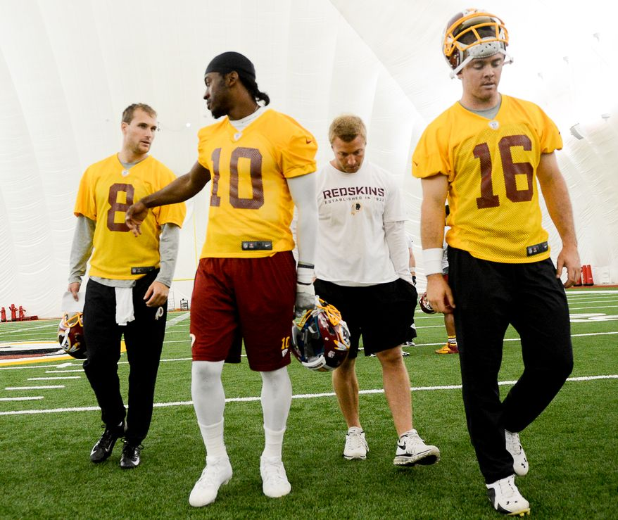 Left to right: Washington Redskins quarterbacks Kirk Cousins, quarterback Robert Griffin III (10), offensive coordinator and quarterbacks coach Sean McVay, and Colt McCoy (16) leave the field after the Washington Redskins hold their Organized Team Activities at Redskins Park, Ashburn, Va., Thursday, May 29, 2014. (Andrew Harnik/The Washington Times)