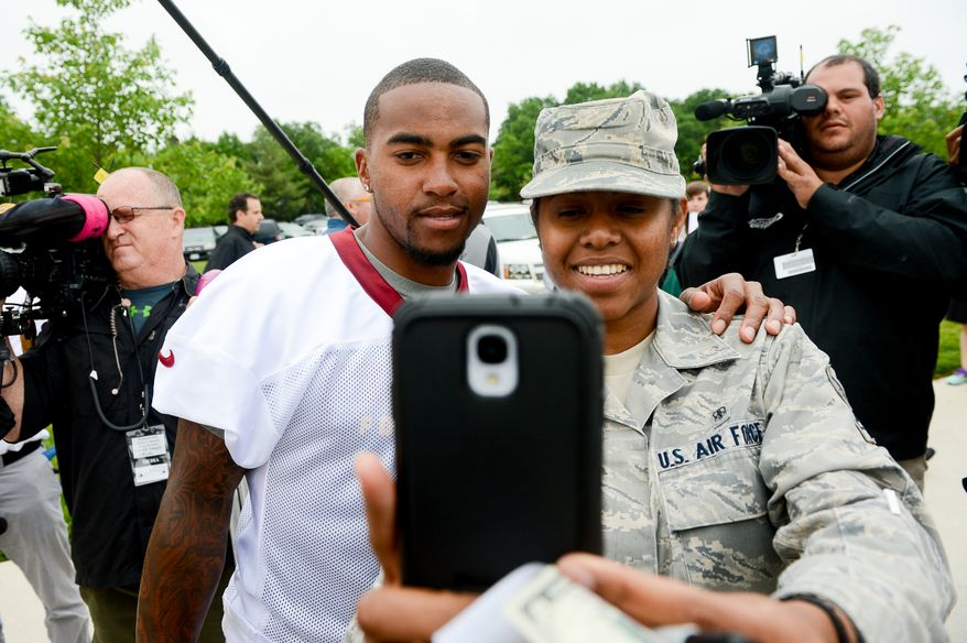 Air Force Senior Airman Melissa Fletcher, right, takes a photo with Washington Redskins wide receiver DeSean Jackson (1) after practice as the Washington Redskins hold their Organized Team Activities at Redskins Park, Ashburn, Va., Thursday, May 29, 2014. (Andrew Harnik/The Washington Times)