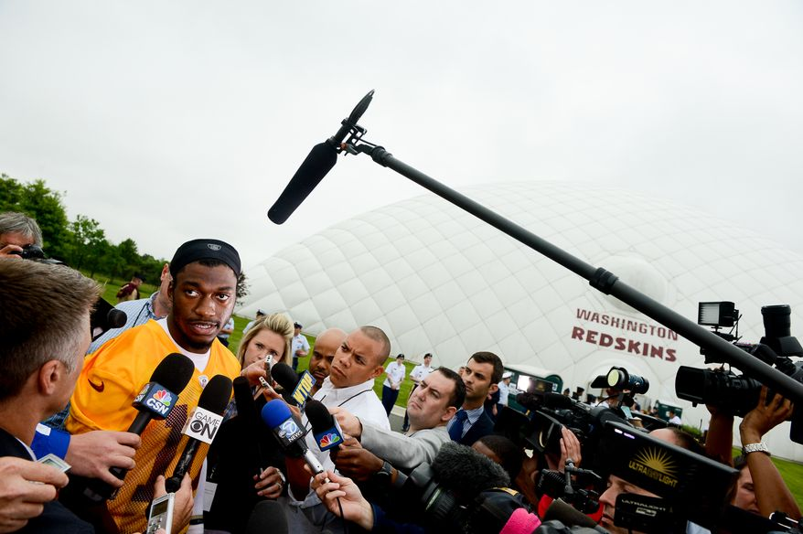 Washington Redskins quarterback Robert Griffin III (10) speaks to reporters after practice as the Washington Redskins hold their Organized Team Activities at Redskins Park, Ashburn, Va., Thursday, May 29, 2014. (Andrew Harnik/The Washington Times)