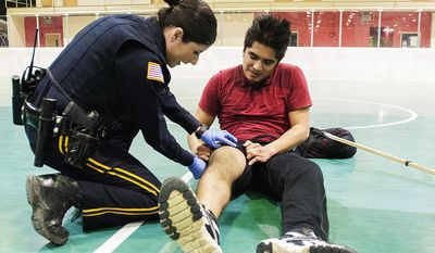 In this April 3, 2014 photo, Northern Illinois University police officer Maria Christiansen checks on NIU senior Juan Martinez during a floor hockey game on campus before calling paramedics to assist in DeKalb, Ill.  Christiansen, a survivor of the Feb. 14, 2008 NIU school shooting that injured 21 and killed five students, works the night shift on campus patrol. (AP Photo/Daily Chronicle, Danielle Guerra)  MANDATORY CREDIT