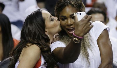 Adrienne Bosh, left, wife of Miami Heat player Chris Bosh, kisses tennis player Serena Williams as Willians takes a photo during the first half Game 6 in the NBA basketball playoffs Eastern Conference finals between the Indiana Pacers and the Heat, Friday, May 30, 2014, in Miami. (AP Photo/Lynne Sladky)