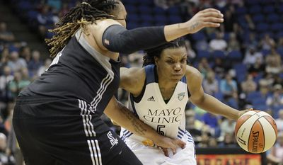 Minnesota Lynx guard Tan White (5) drives the ball around San Antonio Stars forward Danielle Adams, left, in the first half of a WNBA basketball game on Friday, May 30, 2014, in Minneapolis. (AP Photo/Stacy Bengs)