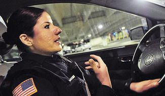 In this April 3, 2014 photo, Northern Illinois University police officer Maria Christiansen explains where she was hit with shotgun pellets during the Feb. 14, 2008 NIU school shooting in which the shooter killed 5 students and injured 21 before turning the gun on himself in DeKalb, Ill. Christiansen has worked as a NIU police officer for 5 years. (AP Photo/Daily Chronicle, Danielle Guerra)  MANDATORY CREDIT