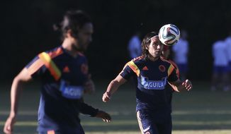 Colombia's player Radamel Falcao, right, trains with teammate Eder Alvarez Balanta in Buenos Aires, Argentina, Wednesday, May 28, 2014. Colombia's national soccer team is hoping Falcao will be able to play at the World Cup after his knee injury. Brazil is hosting the international soccer tournament starting in June. (AP Photo/Sergio Llamera)