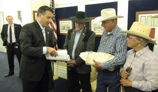 Nevada Gov. Brian Sandoval, left, accepts petitions from Assemblyman Ira Hansen, R-Sparks, and Battle Mountain ranchers Pete and Lynn Tomara on Friday, May 30, 2014, in Carson City, Nev. About 40 ranchers rode horses to the governor's office to deliver the petitions critical of federal management of grazing on public lands. (AP Photo/Sandra Chereb)