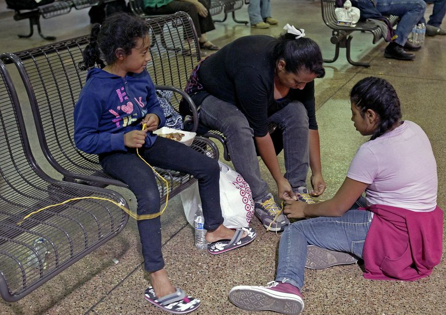 Elana Carmen, middle, with her daughters Abigail, right, and Ayala, of El Salvador, tie their shoes with yellow rope for shoe laces, Thursday, May 29, 2014 at the Greyhound bus terminal in Phoenix. About 400 mostly Central American women and children caught crossing from Mexico into south Texas were flown to Arizona this weekend after border agents there ran out of space and resources.  Officials then dropped hundreds of them off at Phoenix and Tucson Greyhound stations, overwhelming the stations and humanitarian groups who were trying to help. (AP Photo/Rick Scuteri)