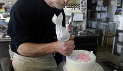 **FILE** Masterpiece Cakeshop owner Jack Phillips decorates a cake inside his store  in Lakewood, Colo., on March 10, 2014. Colorado's Civil Rights Commission in March upheld a judge's ruling that Phillips cannot refuse to make wedding cakes for same-sex couples, despite Phillips' cited religious opposition to same sex marriage. The panel says doing so violates state laws prohibiting businesses from discriminating against gay people. (Associated Press)