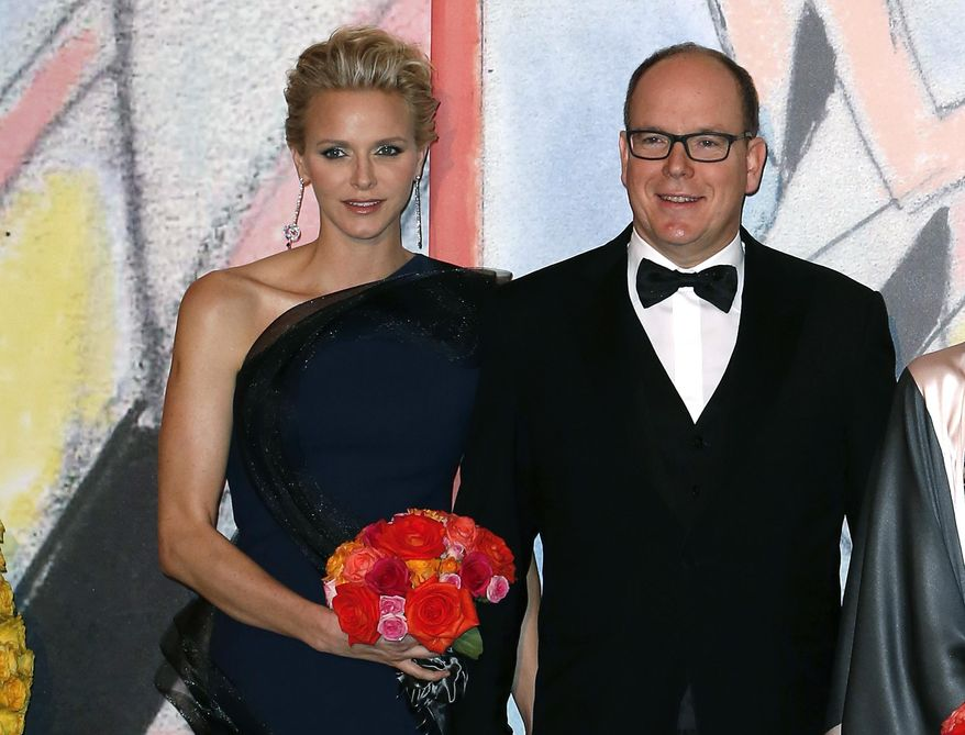 """FILE-  In this Saturday, March 29, 2014 file photo, Prince Albert II of Monaco, and his wife Princess Charlene pose for photographers as they arrive at the Rose Ball for the 50th anniversary of the Princess Grace Foundation, in Monaco. Princess Charlene of Monaco, who married Prince Albert II in 2011, has announced she is pregnant with the pair's first baby. The 36-year-old South African former Olympic swimmer and her husband issued a statement expressing their """"immense joy"""" at the news. The short statement says that the birth is expected before the end of the year, which means the princess is at least three months pregnant. (AP Photo, file)"""