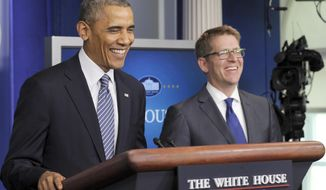 President Barack Obama shares a laugh as he makes a surprise visit into the Brady Press Briefing Room in Washington, Friday, May 30, 2104, to announce that White House press secretary Jay Carney, right, will be stepping down later next month. The president announced Carney's departure in a surprise appearance at in the White House press briefing room Friday. He said principal deputy press secretary Josh Earnest will take over the job. (AP Photo/Susan Walsh)