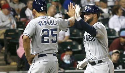 San Diego Padres' Will Venable (25) greets Yonder Alonso at home after they both scored on Alonso's home run off Chicago White Sox relief pitcher Javy Guerra during the eighth inning of an interleague baseball game Friday, May 30, 2014, in Chicago. (AP Photo/Charles Rex Arbogast)