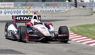Driver Helio Castroneves takes the second turn during a practice session for the IndyCar Detroit Grand Prix auto race on Belle Isle in Detroit, Friday, May 30, 2014. (AP Photo/Bob Brodbeck)