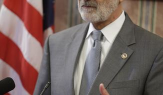 Mayor Frank Jackson makes a statement regarding the grand jury announcement regarding the deaths of Timothy Russell and Malissa Williams Friday, May 30, 2014, in Cleveland. A grand jury on Friday indicted six police officers involved in a November 2012 car chase that ended in the deaths of two unarmed people, was decried by critics as a racially motivated execution and is part of a wide-ranging federal investigation. The grand jury indicted a patrol officer on two charges of manslaughter and five supervisors on charges of dereliction of duty for failing to control the chase. (AP Photo/Tony Dejak)