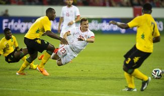 Joel Grant, Wes Morgan and Lloyd Doyley, from left, of Jamaika stop Xherdan Shaqiri of Switzerland, during the international friendly soccer match between Switzerland and Jamaica at the swissporarena in Lucerne, Switzerland, Friday, May 30, 2014. Switzerland are preparing for the upcoming FIFA soccer World Cup in Brazil starting on 12 June. (AP Photo/Keystone, Sigi Tischler)