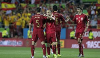 Spain's Andres iniesta, second left, celebrates with teammate Cesar Azpilicueta, left, after scoring against Bolivia during their friendly soccer match in Seville, Spain on Friday, May 30. 2014. (AP Photo/Miguel Angel Morenatti)