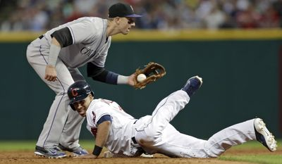 Cleveland Indians' Michael Brantley dives safely back into second base as Colorado Rockies shortstop Troy Tulowitzki takes the pickoff throw in the fifth inning of a baseball game Friday, May 30, 2014, in Cleveland. (AP Photo/Mark Duncan)