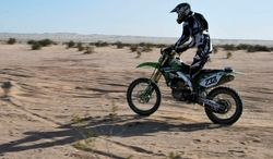 """ADVANCE FOR WEEKEND EDITIONS, JUNE 1-2 - In this April, 2014 photo provided by Monster Energy, double-amputee Jesse Williamson races in the Imperial Valley 250 in Plaster City, Calif.  Williamson's legs. PTSD haunted him. Addiction left him apathetic. Climbing back onto a dirt bike and racing across the desert changed everything for the former Marine. """"I feel alive again,"""" Williamson said. """"It's like a new experience every time."""" (AP Photo/Monster Energy)"""