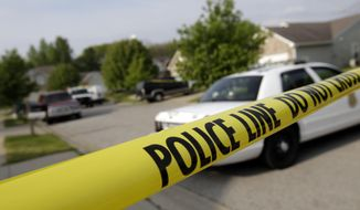 Police tape blocks the street in front of the scene of a shooting that left three dead the previous night in the Lakeside Manor neighborhood of Indianapolis Tuesday, May 20, 2014 in Indianapolis. The Indiana capital has already recorded 60 homicides and is on pace to have its deadliest year in eight years.  (AP Photo/AJ Mast)