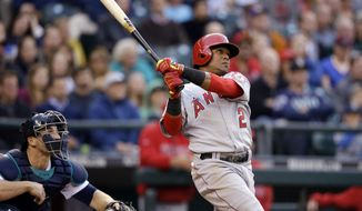 Los Angeles Angels' Erick Aybar watches his three-run home run in front of Seattle Mariners catcher Mike Zunino in the fourth inning of a baseball game Thursday, May 29, 2014, in Seattle. (AP Photo/Elaine Thompson)