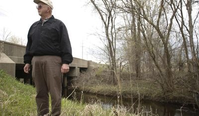 Richard Sharland from Plymouth stands on the edge of Johnson Creek on Thur., May 1, 2014 near the old Detroit House of Corrections facility in Plymouth. The creek is the dividing line between two parcels of land under question in reference to land acquisition between Plymouth and Wayne Townships. (AP Photo/Detroit Free Press, Tim Galloway)