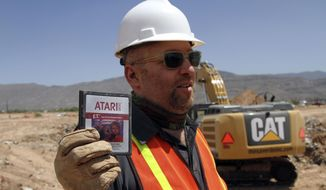 """Film Director Zak Penn shows a box of a decades-old Atari """"E.T. the Extra-Terrestrial"""" game found in a dumpsite in Alamogordo, N.M., in this April 26, 2014, file photo, Producers of a documentary dug in an southeastern New Mexico landfill in search of millions of cartridges of the Atari """"E.T. the Extra-Terrestrial"""" game that has been called the worst game in the history of video gaming and were buried there in 1983. (AP Photo/Juan Carlos Llorca)"""