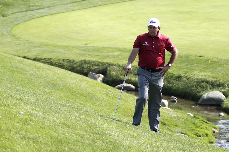 Phil Mickelson reacts to leaving his chip shot short on the 17th hole during the first round of the Memorial golf tournament Thursday, May 29, 2014, in Dublin, Ohio. (AP Photo/Jay LaPrete)