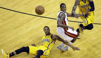 Indiana Pacers forward Paul George, right, and Miami Heat guard Mario Chalmers, center, look back as Pacers guard George Hill (3) loses the ball during the second half of Game 6 in the NBA basketball playoffs Eastern Conference finals on Friday, May 30, 2014, in Miami. (AP Photo/Wilfredo Lee)