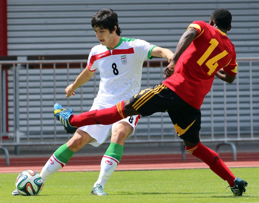 Iran's Sardar Azmoun, left, challenges for a ball with Vadoi, right, of Angola during a friendly soccer match between Iran and Angola, in Hartberg, Austria, Friday, May 30, 2014. (AP Photo/Ronald Zak)