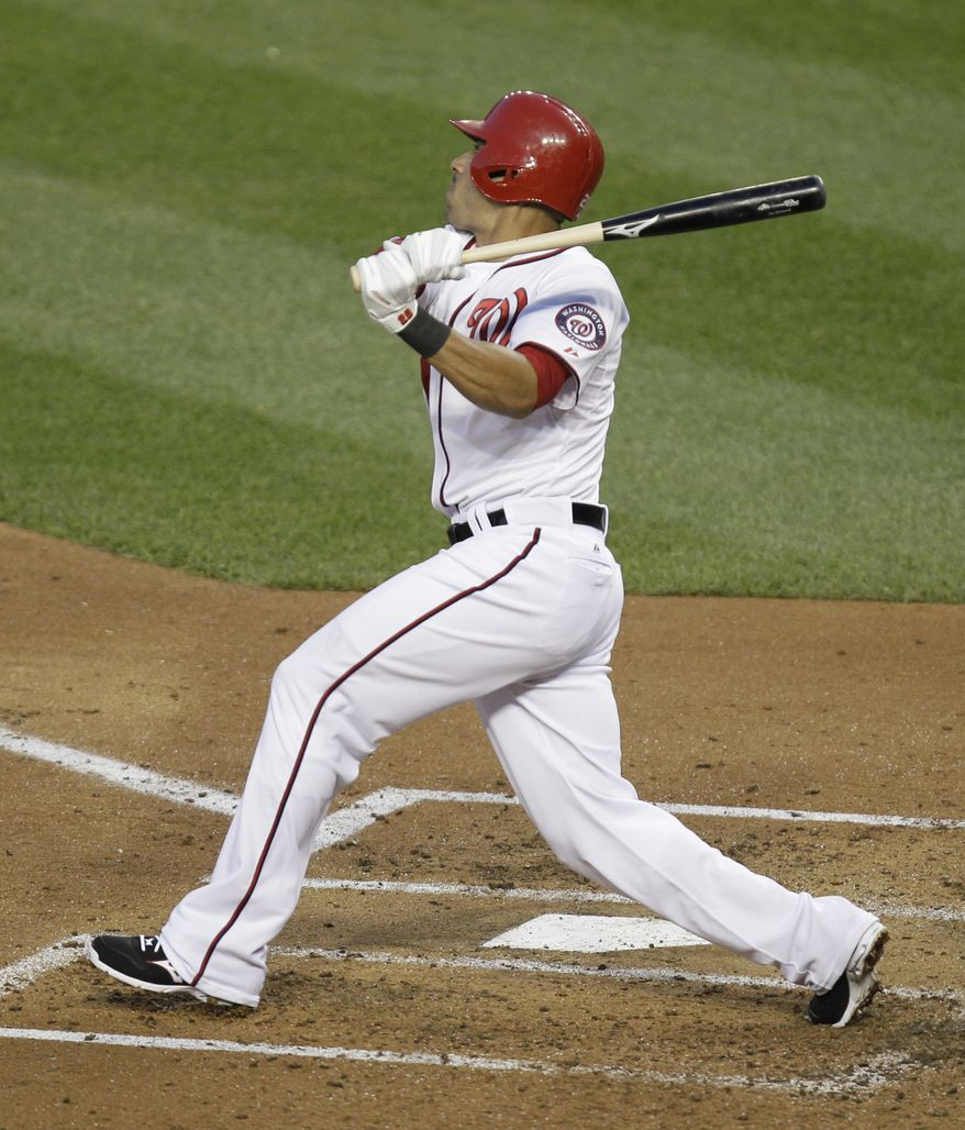 Washington Nationals' Ian Desmond follows through on a three-run home run during the fourth inning of a baseball game against the Texas Rangers, Friday, May 30, 2014, in Washington. (AP Photo/Luis M. Alvarez)