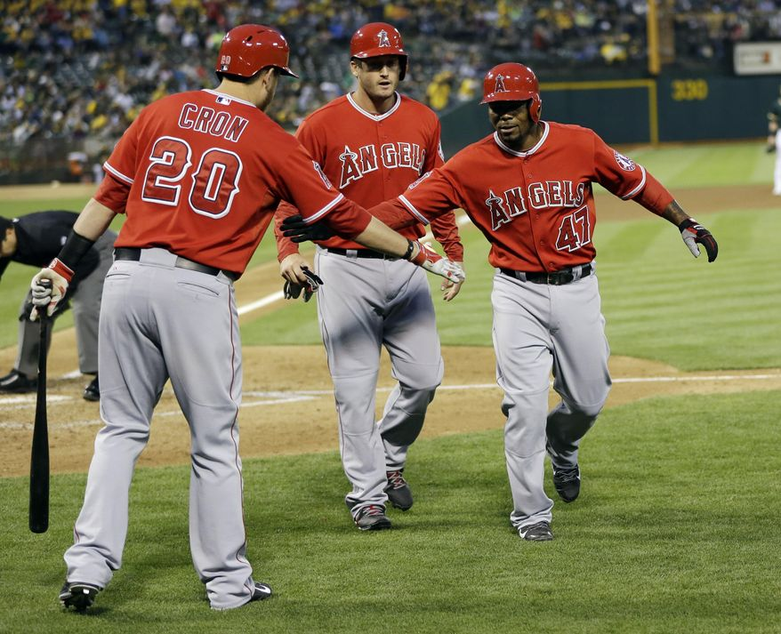 Los Angeles Angels' Howie Kendrick, right, celebrates his two-run home run with teammates David Freese, center, and C.J. Cron (20) during the fourth inning of a baseball game against the Oakland Athletics on Friday, May 30, 2014, in Oakland, Calif. (AP Photo/Marcio Jose Sanchez)