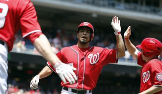 Washington Nationals' Anthony Rendon, center, celebrates his solo home run during the first inning of a baseball game against the Texas Rangers at Nationals Park Saturday, May 31, 2014, in Washington. (AP Photo/Alex Brandon)