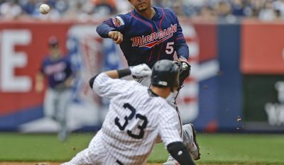 Minnesota Twins shortstop Eduardo Escobar (5) throws out New York Yankees' Brendan Ryan at first base after forcing out Kelly Johnson (33) for a double play during the second inning of a baseball game Saturday, May 31, 2014, in New York.  (AP Photo/Frank Franklin II)