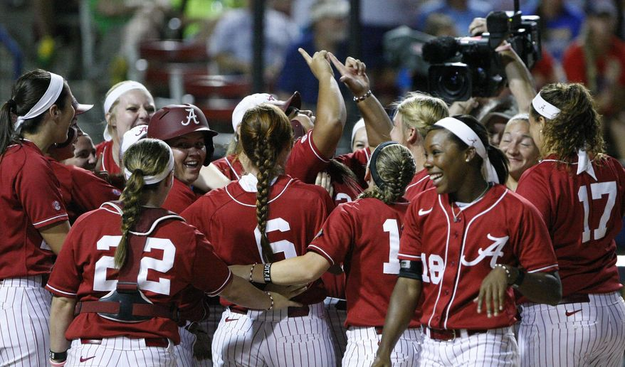 Alabama's Leona Lafaele, center, celebrates with teammates after hitting a two-run home run against Kentucky during the second inning of an NCAA Women's College World Series softball tournament game in Oklahoma City, Friday, May 30, 2014. (AP Photo/Alonzo Adams)