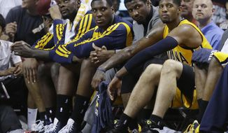 Indiana Pacers guard Lance Stephenson, left, center Ian Mahinmi, second from left, and forward Paul George, right, sit on the bench during the second half Game 6 in the NBA basketball playoffs Eastern Conference finals, Friday, May 30, 2014, in Miami. The Miami Heat defeated the  Pacers 117-92 to advance to the NBA Finals. The player second from right is not identified. (AP Photo/Lynne Sladky)