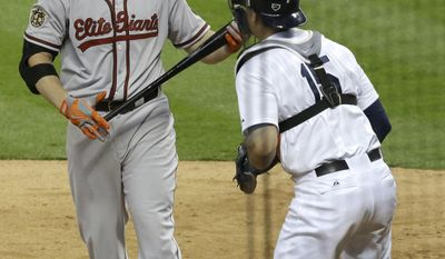 Baltimore Orioles' Chris Davis, left, reacts to being called out on strikes as Houston Astros catcher Jason Castro heads to the field to celebrate a 2-1 win in Major League baseball's annual Civil Rights Game Friday, May 30, 2014, in Houston. (AP Photo/Pat Sullivan)