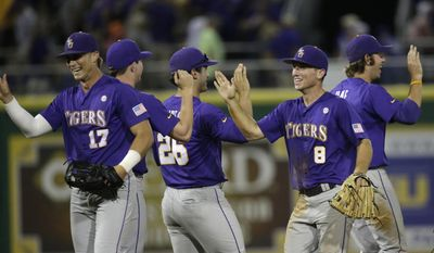 LSU outfielder Jared Foster (17), catcher Chris Chinea (26) and infielder Alex Bregman (8) celebrate their 5-1 victory over Houston after an NCAA college baseball regional tournament game in Baton Rouge, La., Saturday, May 31, 2014. (AP Photo/Gerald Herbert)