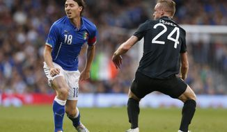 Italy's Riccardo Montolivo, left, is tackled by Republic of Ireland's Alex Pearce and is injured from the tackle during their international friendly soccer match at Craven Cottage, London, Saturday, May 31, 2014. (AP Photo/Sang Tan)