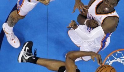 Oklahoma City Thunder's Jeremy Lamb, left, and Reggie Jackson, right and San Antonio Spurs forward Boris Diaw, bottom, watch the ball in the first half of Game 6 of the Western Conference finals NBA basketball playoff series in Oklahoma City, Saturday, May 31, 2014. (AP Photo/Sue Ogrocki)