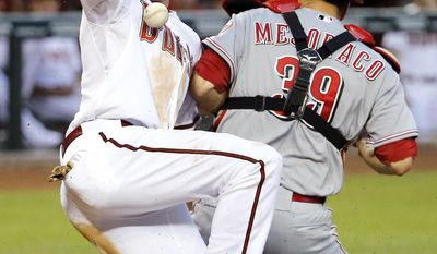 Arizona Diamondbacks' A.J. Pollock scores on a ball hit by Gerardo Parra as Cincinnati Reds catcher Devin Mesoraco can't handle the throw during the third inning of a baseball game, Friday, May 30, 2014, in Phoenix. (AP Photo/Matt York)