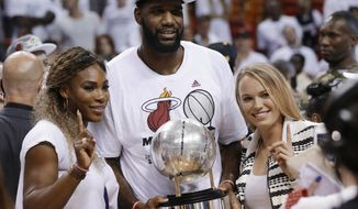 Tennis players Serena Williams, left and Caroline Wozniacki pose with Miami Heat's Greg Oden and the NBA basketball Eastern Conference championship trophy, Friday, May 30, 2014, in Miami. The Miami Heat defeated the Indiana Pacers 117-92 to advance to the NBA finals. (AP Photo/Lynne Sladky)