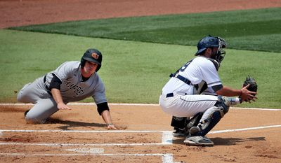 Campbell catcher Matt Parrish. left, slides safe into home plate while Old Dominion catcher Michael Perez, right, waits for the throw during an NCAA college baseball tournament regional game in Columbia, S.C., Saturday, May 31, 2014. (AP Photo/Stephen B. Morton)