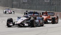 Will Power leads Simon Pagenaud through Turn 1 during the first race of the IndyCar Detroit Grand Prix auto racing doubleheader in Detroit, Saturday, May 31, 2014. (AP Photo/Carlos Osorio)