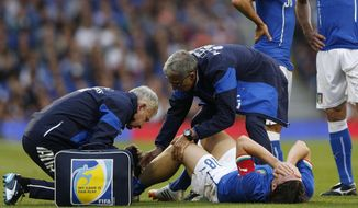 Italy's Riccardo Montolivo, lower right, is being treated after injured from a tackle during their international friendly soccer match against the Republic of Ireland, at Craven Cottage, London, Saturday, May 31, 2014. (AP Photo/Sang Tan)