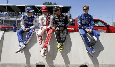 From left, Ryan Briscoe, Scott Dixon, Tony Kanaan and Josef Newgarden sit on a barrier before driver introductions for the first race of the IndyCar Detroit Grand Prix auto racing doubleheader in Detroit, Saturday, May 31, 2014. (AP Photo/Carlos Osorio)