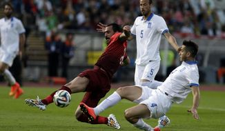 Portugal's Hugo Almeida, left, lunges for the ball against Greece's Kostas Manolas during a friendly soccer match between Portugal and Greece at the National stadium, in Oeiras, near Lisbon, Saturday, May 31, 2014. The game is a warm-up match for both teams ahead the upcoming World Cup in Brazil. (AP Photo/Francisco Seco)