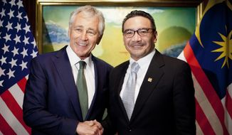 """U.S. Defense Secretary Chuck Hagel, left, meets with Malaysian Defense Minister Hishammuddin Hussein Saturday, May 31, 2014 in Singapore. Hagel warned an international security conference Saturday that the U.S. """"will not look the other way"""" when nations such as China try to restrict navigation or ignore international rules and standards. (AP Photo/Pablo Martinez Monsivais, Pool)"""