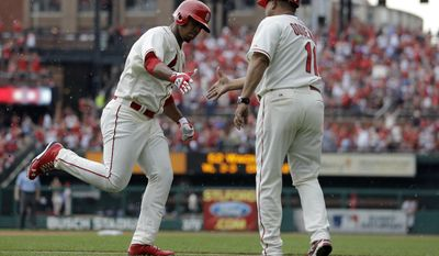 St. Louis Cardinals' Oscar Taveras, left, is congratulated by third base coach Jose Oquendo after hitting a solo home run during the fifth inning of a baseball game Saturday, May 31, 2014, in St. Louis. (AP Photo/Jeff Roberson)