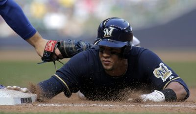 Milwaukee Brewers center fielder Carlos Gomez, right, safely slides back to first base against the Chicago Cubs during the fourth inning of a baseball game Saturday, May 31, 2014, in Milwaukee. (AP Photo/Darren Hauck)