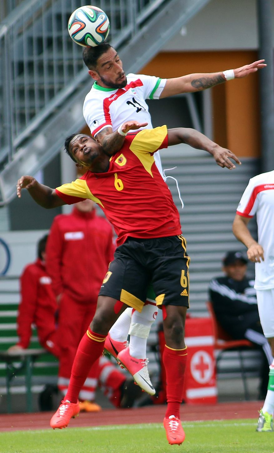 Iran's Ashkan Dejagah, right, challenges for a ball with Joaquim Adao, left, of Angola during a friendly soccer match between Iran and Angola, in Hartberg, Austria, Friday, May 30, 2014. (AP Photo/Ronald Zak)